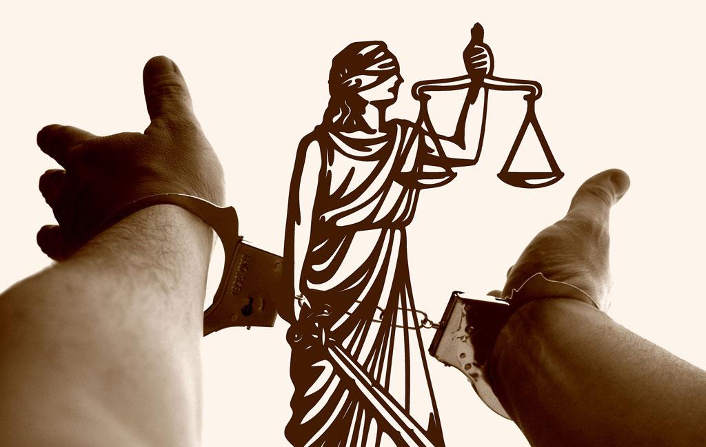 Strafrecht - Hände in Handschellen mit Justitia